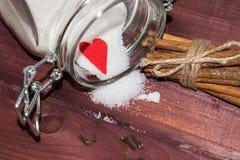 Tarro de cristal con el interior del azúcar adornado con los palillos del corazón y del canela de la tarjeta del día de San Valen Fotografía de archivo libre de regalías
