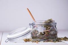 Tarro de cristal con la cuchara seca de la infusión de hierbas y de madera fotografía de archivo libre de regalías