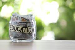 Tarro de cristal con la EDUCACIÓN del dinero y de la etiqueta en la tabla contra fondo borroso imágenes de archivo libres de regalías
