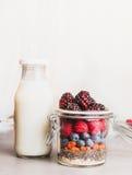 Tarro de cristal con la harina de avena, las semillas de Chia, las bayas de Goji, las bayas frescas y la botella de leche en el f Foto de archivo libre de regalías