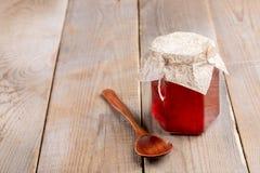 Tarro de cristal con la mermelada de fresa y la cuchara de madera en la tabla de madera rústica vieja foto de archivo libre de regalías