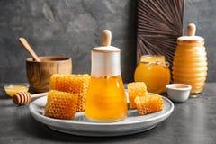 Tarro de cristal con la miel deliciosa y los panales frescos Fotos de archivo libres de regalías