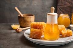 Tarro de cristal con la miel deliciosa y los panales frescos Foto de archivo libre de regalías