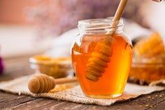 Tarro de cristal con la miel natural y el cazo de madera Foto de archivo libre de regalías