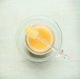 Tarro de cristal con la miel y cazo en fondo azul claro Fotografía de archivo libre de regalías