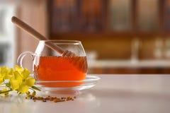 Tarro de cristal con la miel y cazo en la tabla de cocina blanca Imagen de archivo