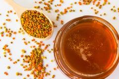 Tarro de cristal con la miel y el polen en una cuchara de madera en un CCB blanco Imagen de archivo libre de regalías