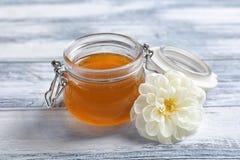 Tarro de cristal con la miel y la flor blanca Fotos de archivo