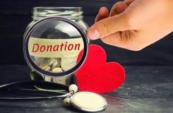 Tarro de cristal con las monedas, corazón y estetoscopio y la inscripción 'donación ' Concepto de la medicina transfusión de sang fotografía de archivo libre de regalías
