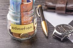 Tarro de cristal con las monedas y billetes de banco del euro con las palabras EDUCACIÓN Pluma, hoja de papel en blanco, cartera  fotos de archivo