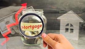 Tarro de cristal con las monedas y la inscripción 'hipoteca 'y para arriba flecha El aumento en tipos de interés en hipotecas Pré foto de archivo