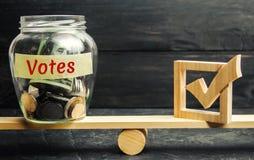 Tarro de cristal con las monedas y votos de las palabras los 'y un checkbox en las escalas Concepto de votación por dinero Soborn imagen de archivo libre de regalías