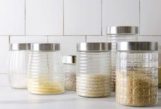 Tarro de cristal con los diversos typies de cereales en la tabla de cocina fotos de archivo
