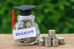 Tarro de cristal con por completo de monedas y de la etiqueta del sombrero de los graduados como Educatio fotografía de archivo libre de regalías