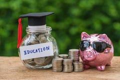 Tarro de cristal con por completo de monedas y de la etiqueta del sombrero de los graduados con Piggyb imagen de archivo libre de regalías