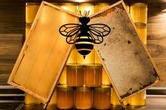Tarro de cristal de la miel amarilla de oro en el marco de los comp del espacio de la copia del primer del tablero de madera vací Foto de archivo
