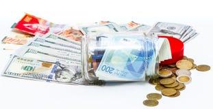Tarro de cristal de la pila de nuevos billetes de banco israelíes de los shekels con los nuevos 200 NIS y de la pila de dólares Imagenes de archivo