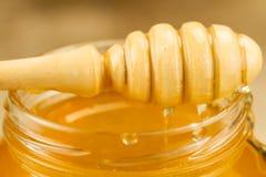 Tarro de cristal de miel con el drizzler en fondo de madera Fotografía de archivo libre de regalías