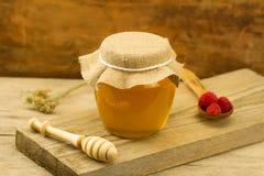 Tarro de cristal de miel con el drizzler, frambuesas, tela del yute, flores en fondo de madera Foto de archivo libre de regalías