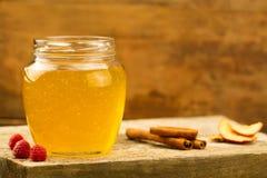 Tarro de cristal de miel del tilo con el drizzler, canela, frambuesas, manzanas Foto de archivo
