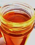 Tarro de cristal Lidless lleno de miel deliciosa foto de archivo libre de regalías