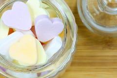 Tarro de cristal llenado de los caramelos del corazón Foto de archivo
