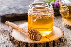 Tarro de cristal de miel con el cazo de la miel en el primer de madera de la rebanada Fotografía de archivo