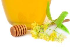 Tarro de cristal de miel fresca del tilo con las flores del tilo en blanco Imagen de archivo