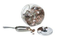 Tarro de cristal por completo de monedas con una cucharada del metal Imagen de archivo