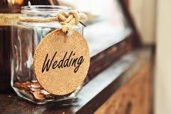 Tarro de cristal retro del vintage con la etiqueta de la boda del lazo de la cuerda del cáñamo y pocas monedas dentro en el conce fotos de archivo