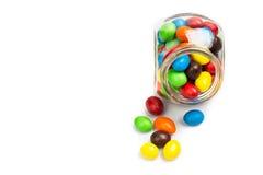 Tarro de cristal transparente con los caramelos de chocolate coloridos en b blanco Imagen de archivo libre de regalías