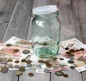 Tarro de cristal vacío y dinero ruso en el piso de madera Imagenes de archivo