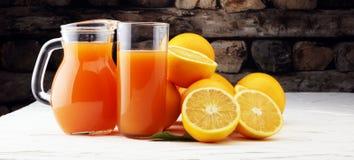 Tarro de cristal de zumo de naranja fresco con las frutas frescas en la tabla blanca Fotos de archivo libres de regalías