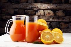 Tarro de cristal de zumo de naranja fresco con las frutas frescas en la tabla blanca Fotos de archivo