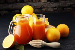 Tarro de cristal de zumo de naranja fresco con las frutas frescas en la tabla oscura Foto de archivo libre de regalías