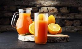 Tarro de cristal de zumo de naranja fresco con las frutas frescas en la tabla oscura Imagen de archivo libre de regalías