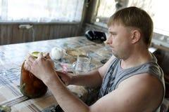 Tarro de la abertura del hombre con los tomates conservados en vinagre foto de archivo libre de regalías
