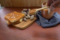 Tarro de la mantequilla de cacahuete con pan y pan en una tabla imagenes de archivo