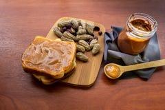 Tarro de la mantequilla de cacahuete con pan y pan en una tabla imagen de archivo libre de regalías