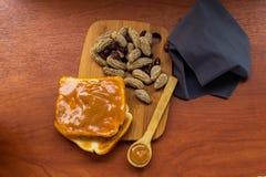 Tarro de la mantequilla de cacahuete con pan y pan en una tabla fotos de archivo libres de regalías