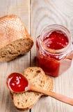 Tarro de la mermelada de fresa, del pan y de la cuchara de madera con el atasco en la tabla de madera imagen de archivo libre de regalías