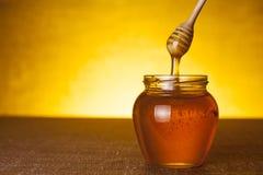 Tarro de la miel con el cazo Fotos de archivo