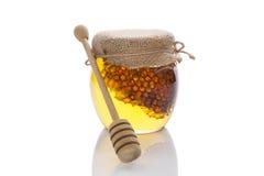 Tarro de la miel con el cazo de madera. Imagenes de archivo