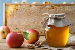 Tarro de la miel con las manzanas frescas Fotos de archivo