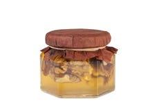 Tarro de la miel con las nueces Foto de archivo libre de regalías