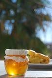 Tarro de la miel con los pasteles Foto de archivo