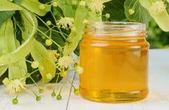 Tarro de la miel del tilo y del tilo floreciente en la tabla de madera Fotos de archivo libres de regalías