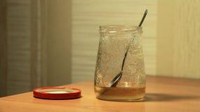 Tarro de la miel en la tabla Imagen de archivo libre de regalías
