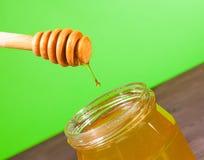 Tarro de la miel en la tabla de madera y fondo verde con el cazo de madera de la miel en el top con la miel del descenso Fotos de archivo libres de regalías