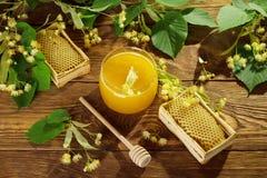 Tarro de la miel, de los panales y de la cuchara del tilo en la tabla Foto de archivo libre de regalías